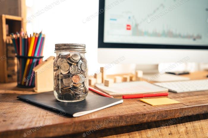 Geld in einem Glasgefäß Auf dem Schreibtisch zu Hause