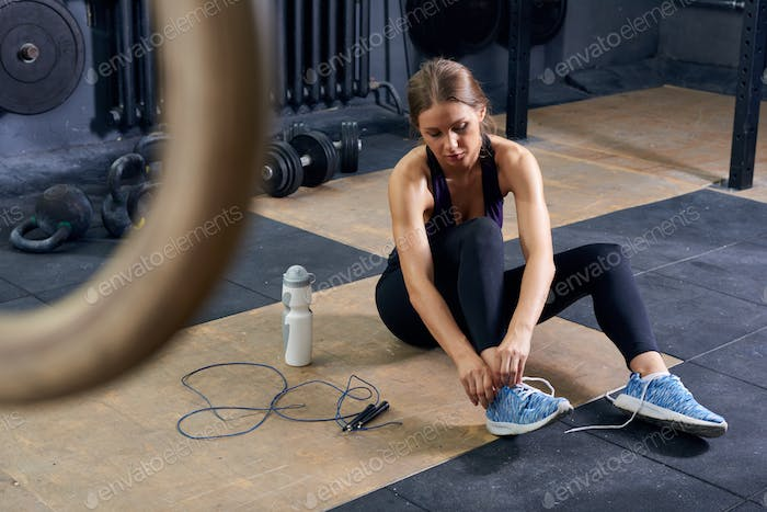 Young Woman Tying Shoes in Gym