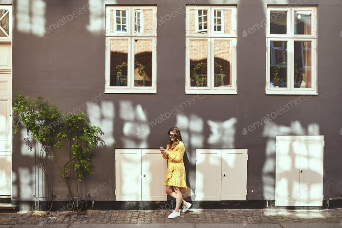 Young woman leaning against a city wall using her cellphone
