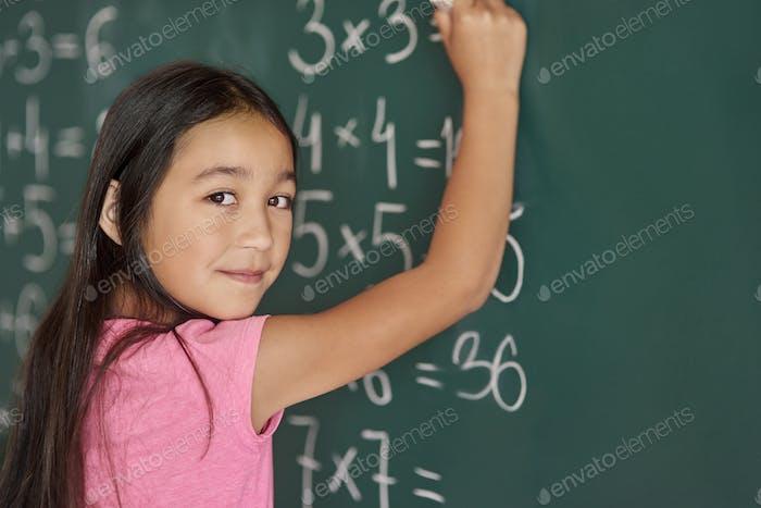 Mädchen machen einige Übungen auf der Tafel