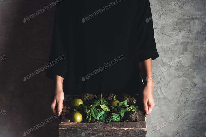 Girl holds a smoothie with spinach, avocado and lime in a vintage box. Wholesome food, vegan, eco