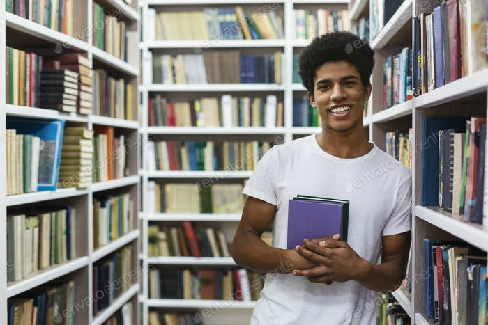 Cheerful african american guy staying between bookshelves, holding book