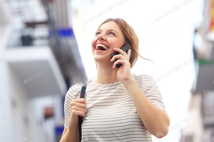 attractive young woman laughing and talking on mobile phonea