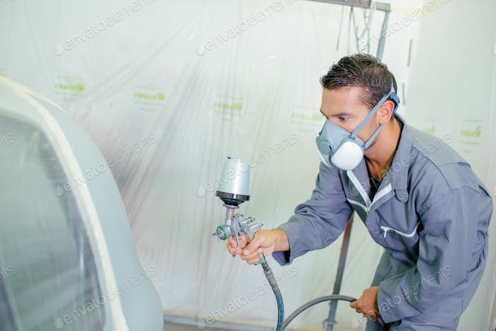 Man respraying car panel