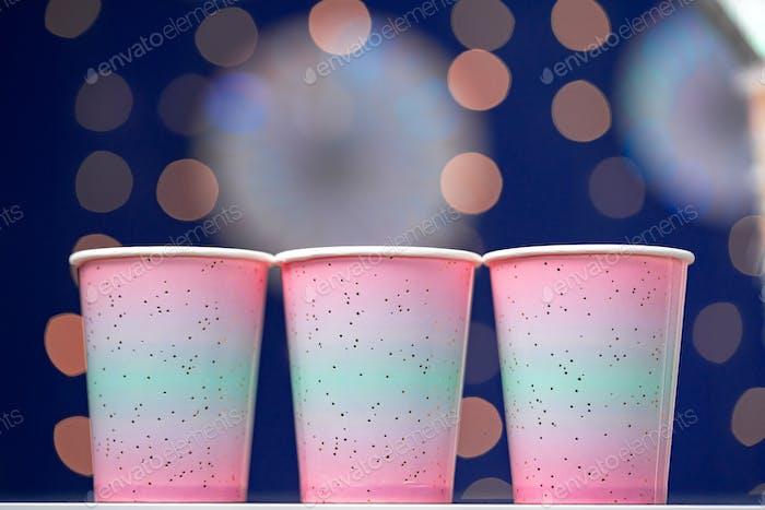 Vasos desechables rosas sobre fondo bokeh azul