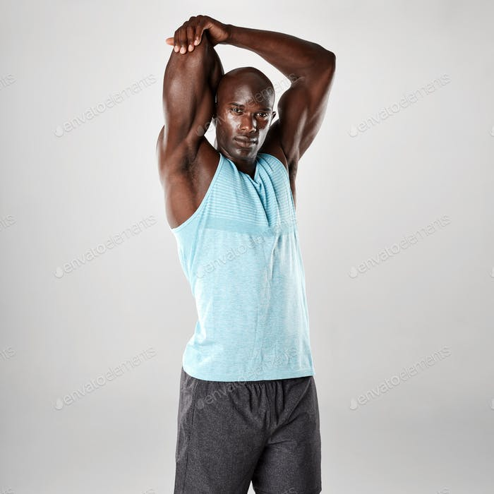 Muscular young man stretching arms