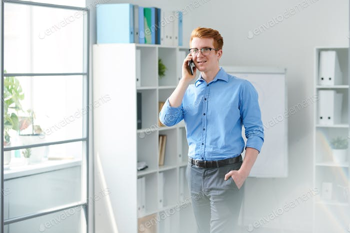 Contemporary young businessman talking on mobile phone to one of clients