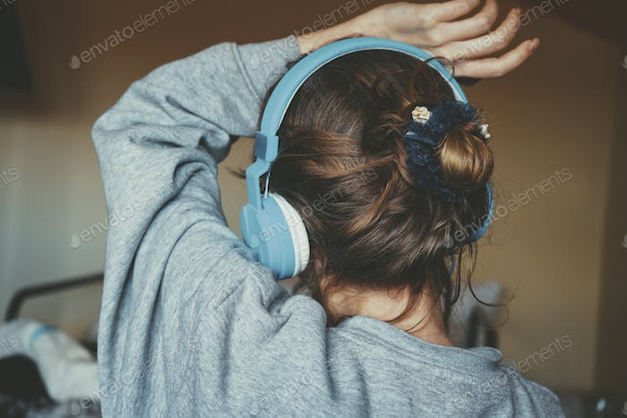 Young woman listening to music and wearing cozy clothes