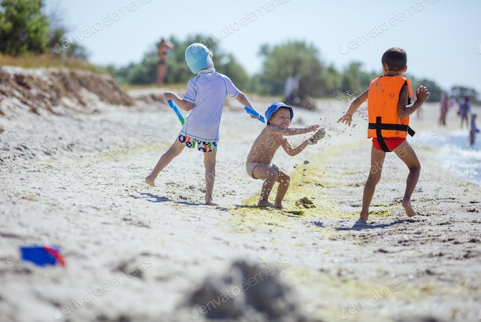 Two older boys throwing sand at younger one