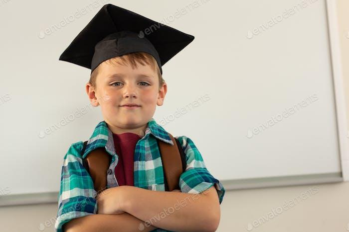 Happy Caucasian boy in graduation cap standing in a classroom at elementary school