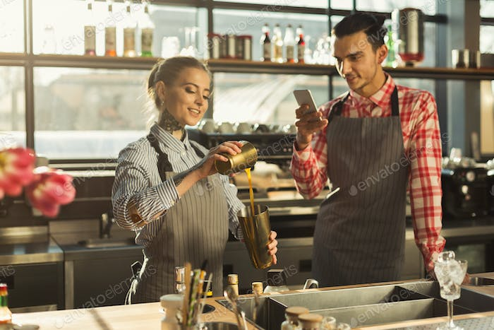 Male and female bartenders at coffee shop counter