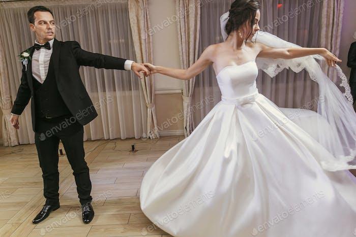 wunderschöne Braut und stilvolle Bräutigam emotional tanzen bei Hochzeitsempfang im Restaurant