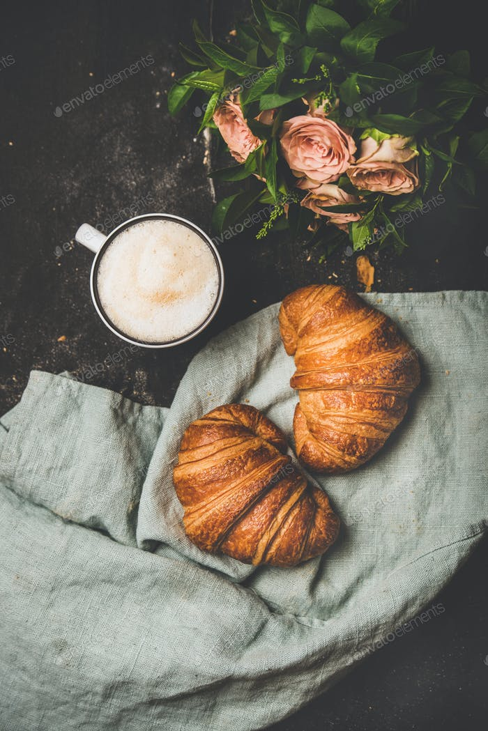 Coffee break with cappuccino, croissants and spring flowers