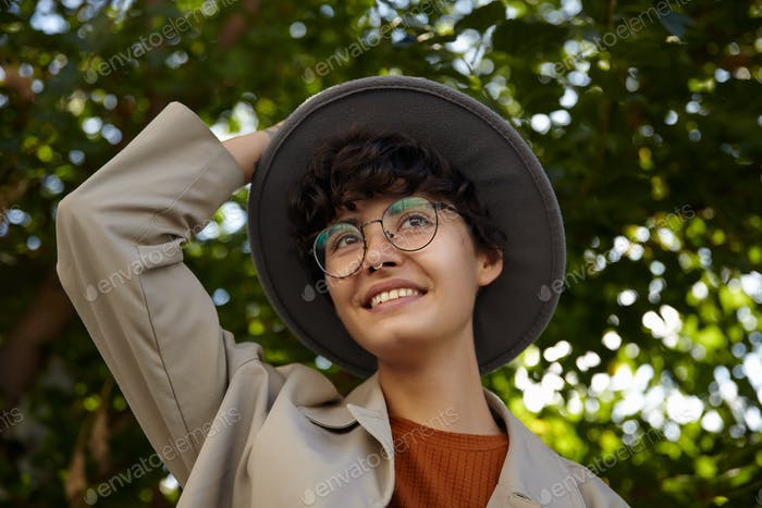 Pleasant looking smiling young curly female with short haircut holding her wide grey hat