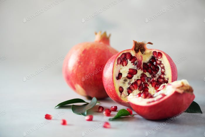 Ripe pomegranate fruit with green leaves on grey concrete background. Banner with copy space