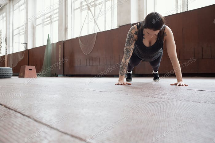 young Caucasian woman with tattooed arm doing plank in sports hall