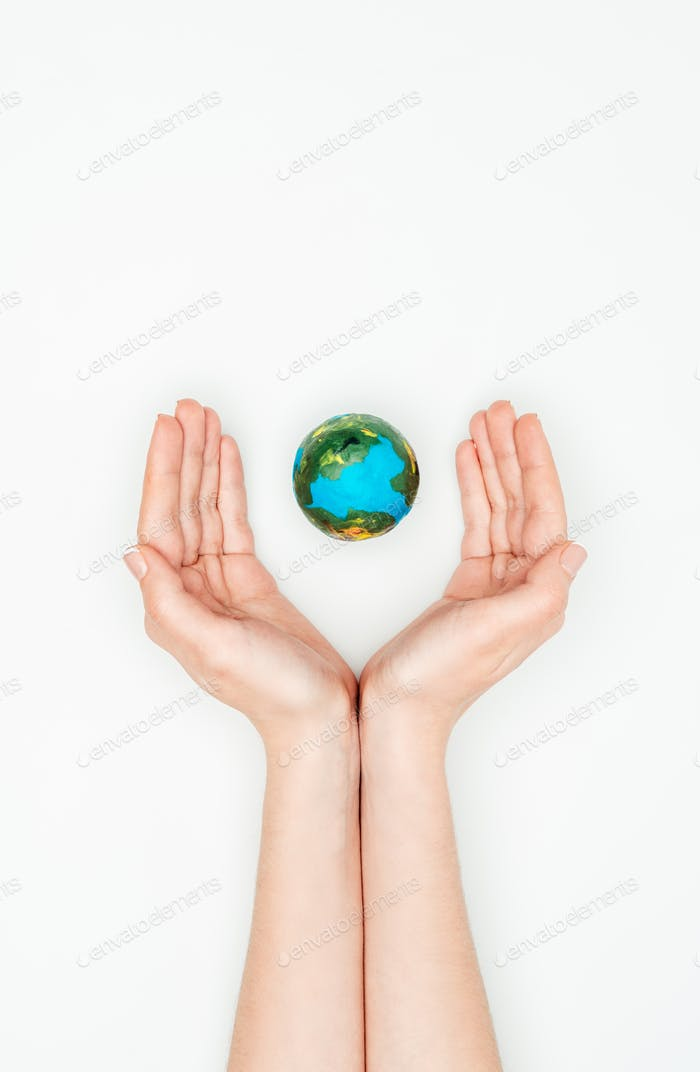cropped image of woman holding hands around earth model isolated on white, earth day concept