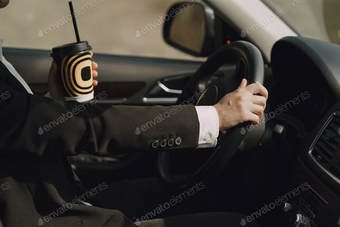 Businesswoman sitting inside a car and drinksa coffee