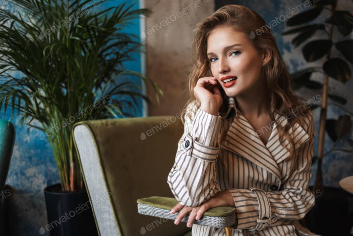 Young smiling pretty woman with wavy hair in striped trench coat