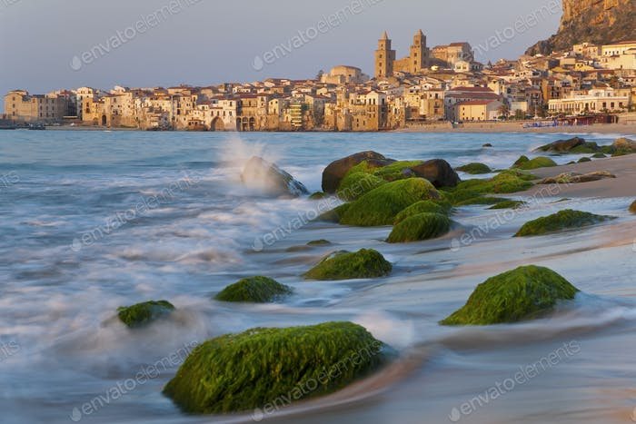View along coastline with sandy beach, rocks covered in green algae, city in the distance.