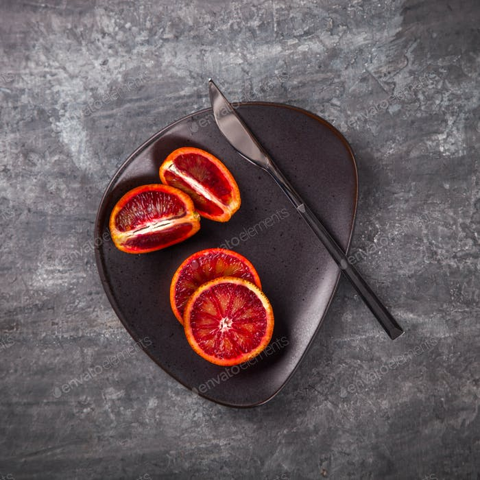 Bloody oranges cut in half on a plate with knife