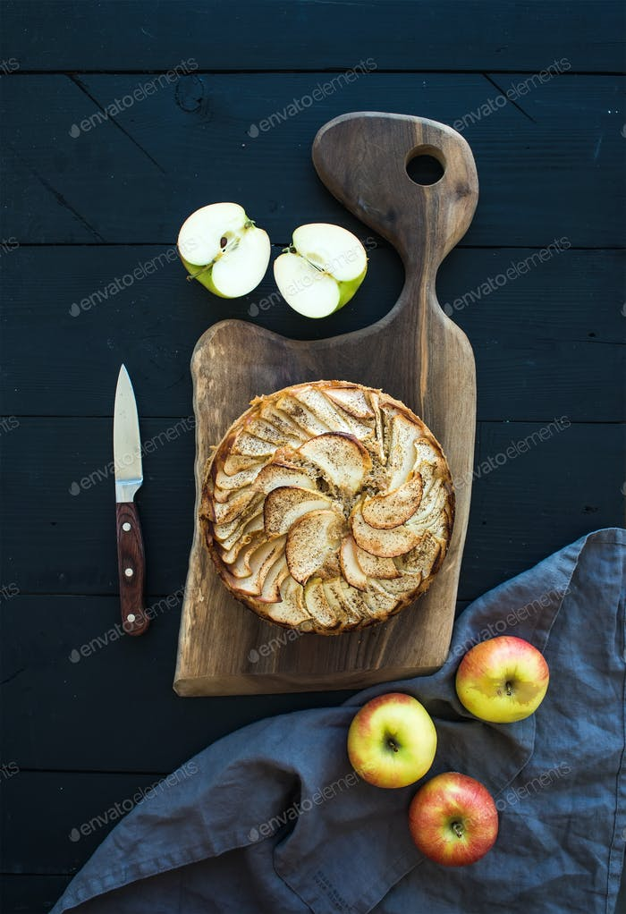 Apple pie on dark chopping board over black wooden background, top view.