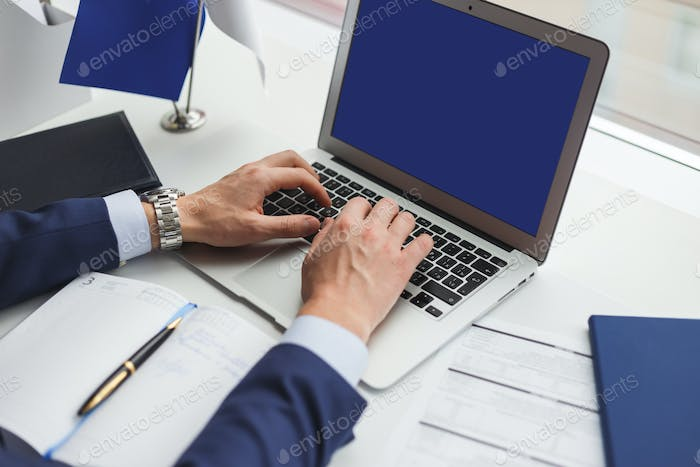 Businessman at work uses laptop with blank screen for pasting any content