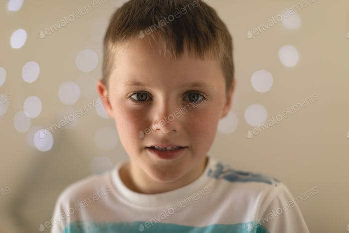 Portrait of innocent boy sitting in bedroom at home