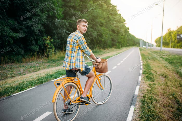 Young man on yellow vintage bicycle with basket