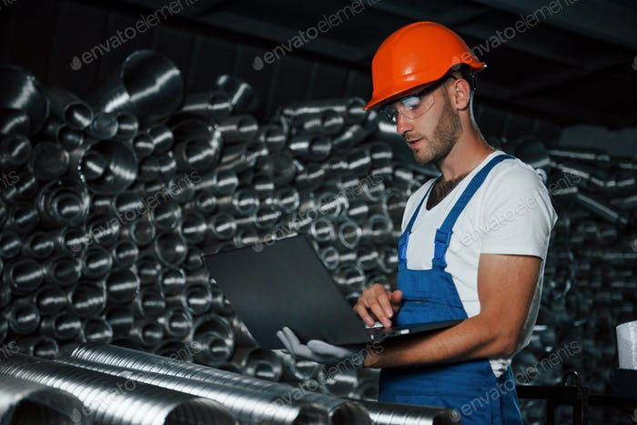 In protective eyewear. Man in uniform works on the production. Industrial modern technology