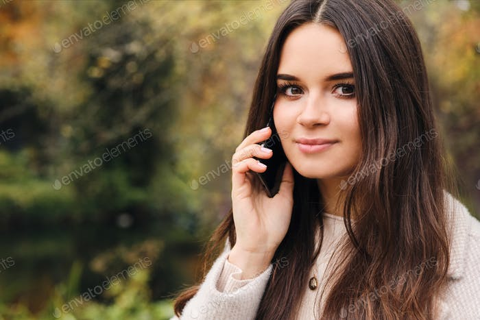 Portrait of brunette girl wistfully looking in camera talking on cellphone in city park