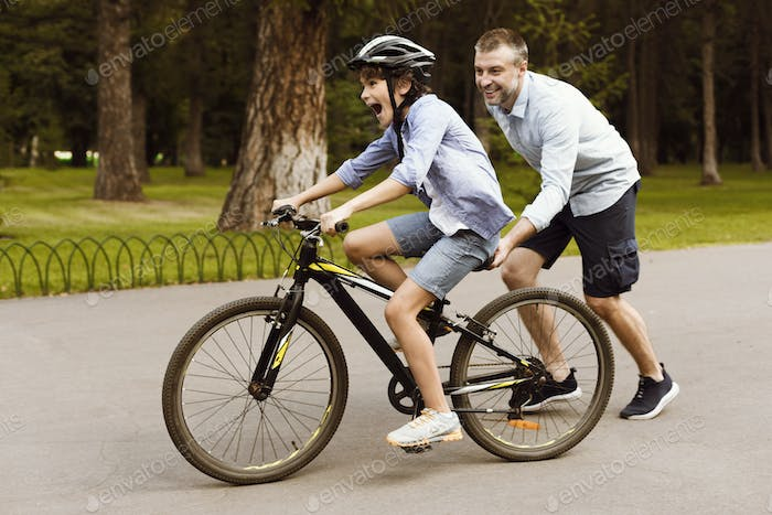 Boy learning to ride bicycle with his supportive dad