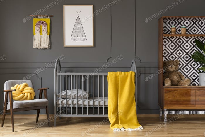 Real photo of a baby room with yellow cot standing between an ar