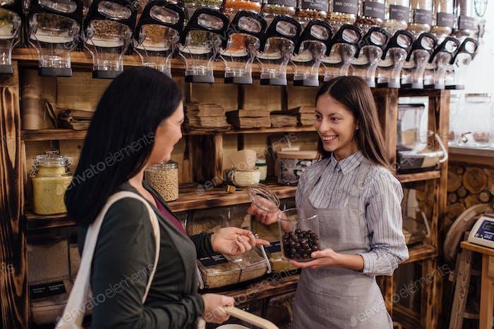 Cheerful shopkeeper helping customer in packaging free shop.