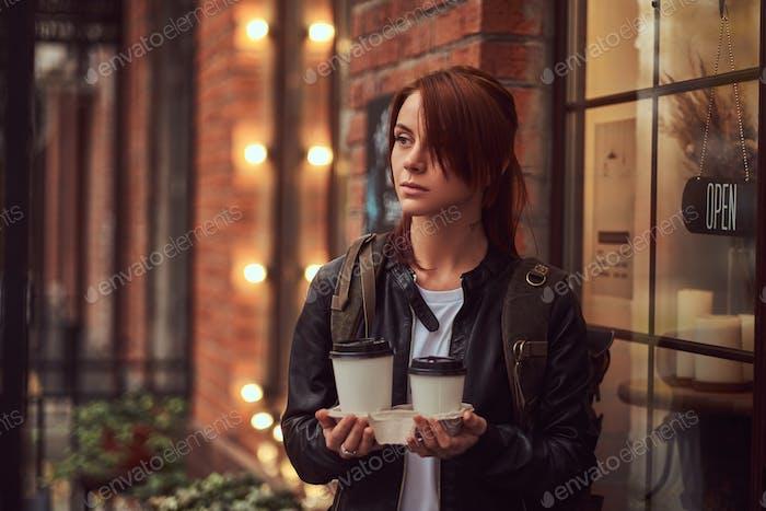 Mujer joven que lleva una chaqueta de cuero que sostiene taza con café para llevar fuera cerca de la cafetería.