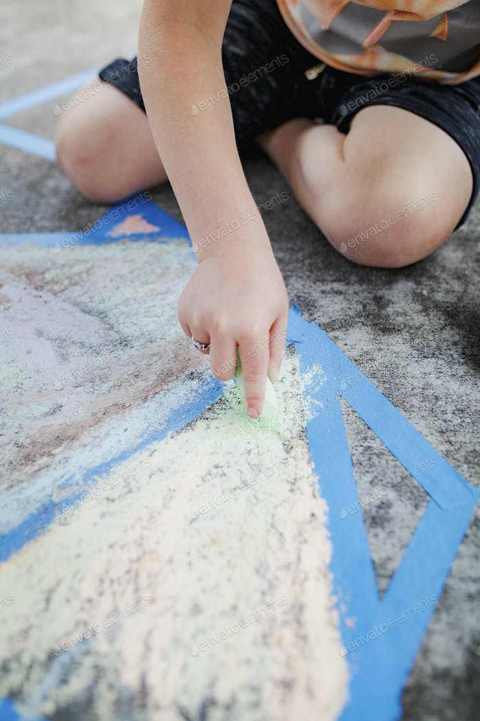 Kid painting concrete ground with a chalk education photography