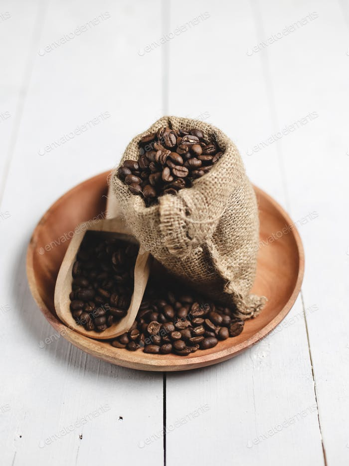 coffee beans in wooden scoop bag and wooden plate with white wood background