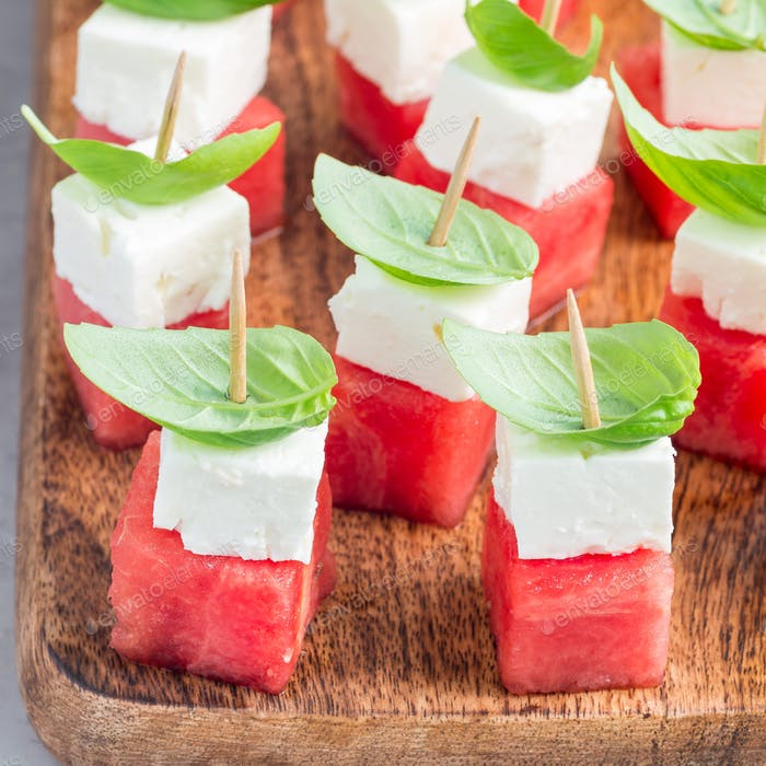 Watermelon salad or caprese with watermelon, feta and basil on a wooden board, square format
