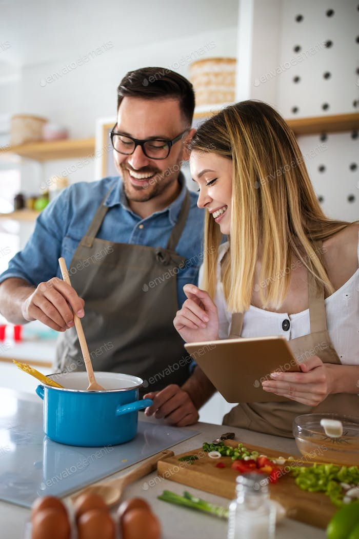 Happy young couple enjoys and having fun preparing healthy meal together at home kitchen