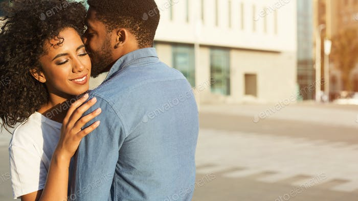 Whispering about love. Man embracing his girlfriend in city
