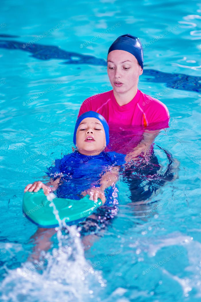 Boy having a swimming lesson with instructor