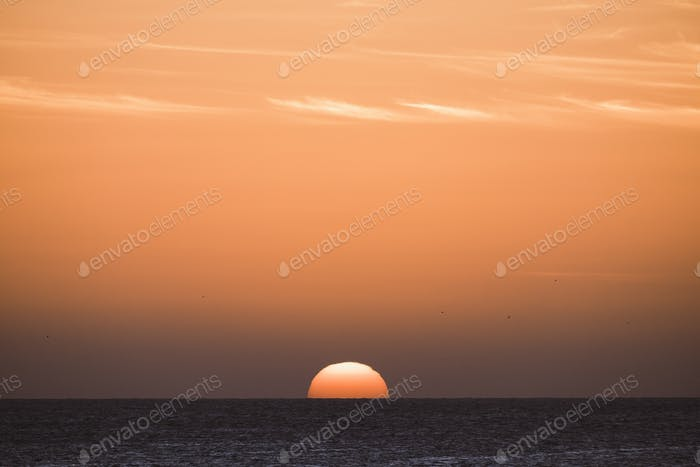 Classic tropical sunset or sunrise on the sea horizon with sun and water touching together