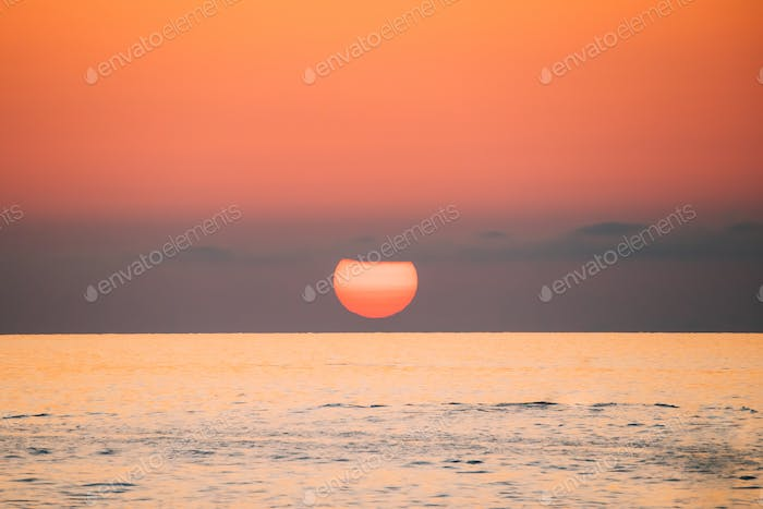 Sundown Above Sea Horizon At Sunset. Natural Sunrise Sky Warm Co
