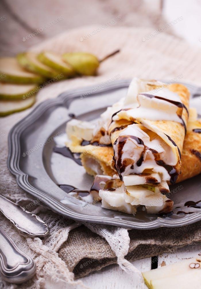 Pfannkuchen mit Birne und Joghurt, gekrönt mit Schokolade.