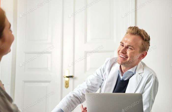 Cheerful cosmetologist consulting young woman sitting at laptop