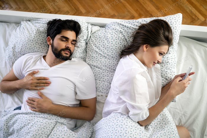 hermosa jóvenes esposa mensajes de texto con amante en smartphone mientras marido es dormir