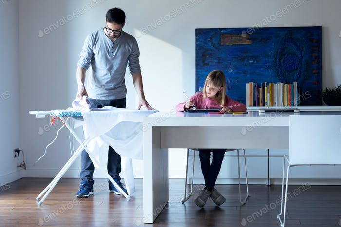 Pretty little girl drawing on notebook while her father ironing a shirt at home.