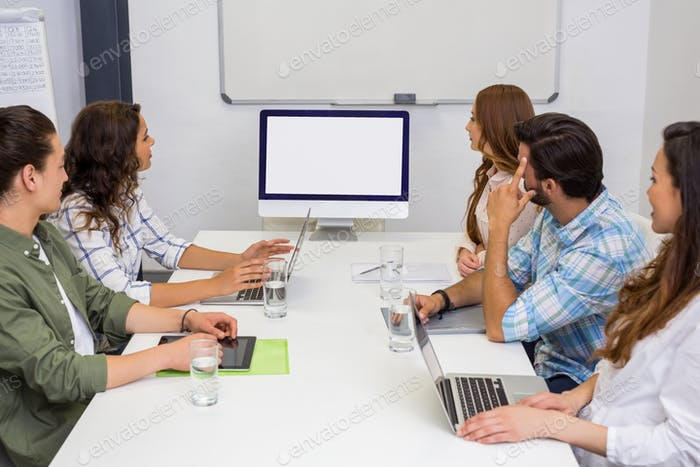 Business team looking at computer screen in the meeting room