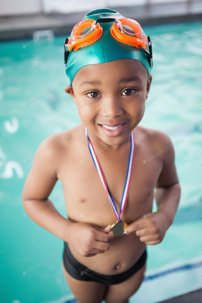 Cute little boy with his medal at the pool at the leisure center