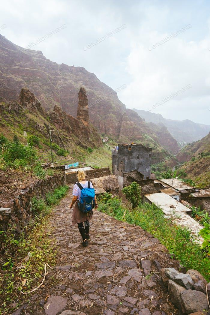 Mädchen mit Rucksack zu Fuß entlang der Trekkingroute zum grünen Xo-Xo Tal. Berggipfel und